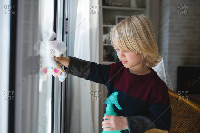 Boy cleaning window with rag cloth at home