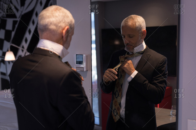 Businessman tying a tie in front of a mirror in hotel room