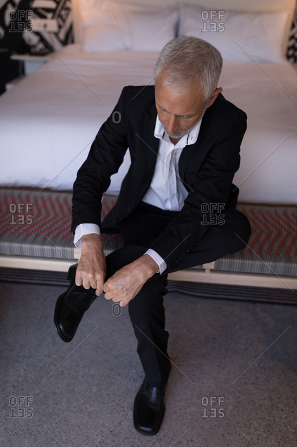 Businessman tying his shoelace in hotel room