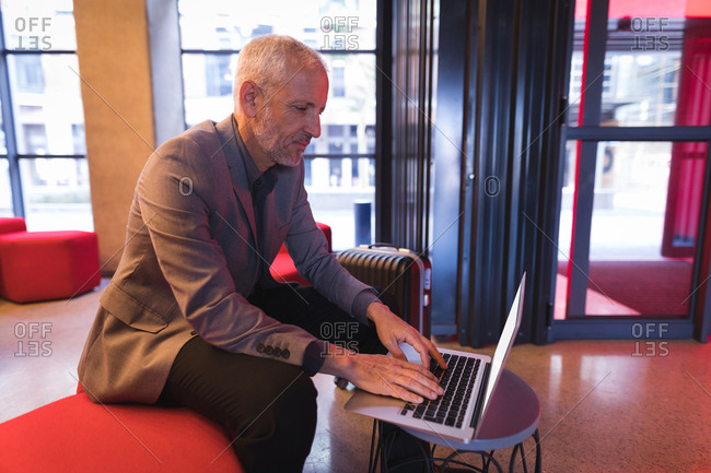 Businessman using laptop in the lobby at hotel