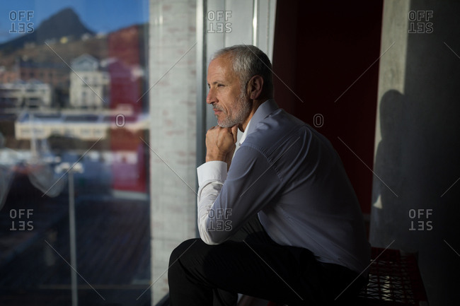 Thoughtful businessman looking through window of hotel room
