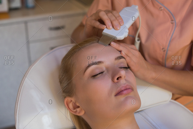 Beautician using ultrasonic scrubber on female customer in parlor