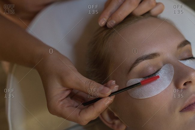 Beautician giving eyelash extension treatment to female customer in parlor