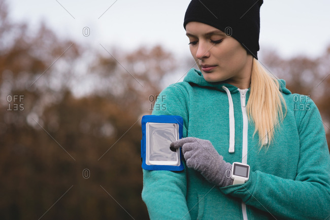 Young woman using mobile phone with arm band in the park