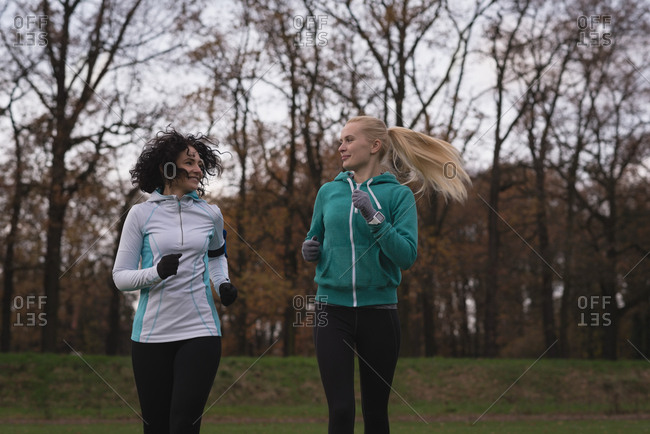 Two young female friends jogging in the park