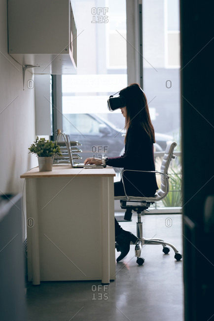 Executive working on laptop while using virtual reality headset in office