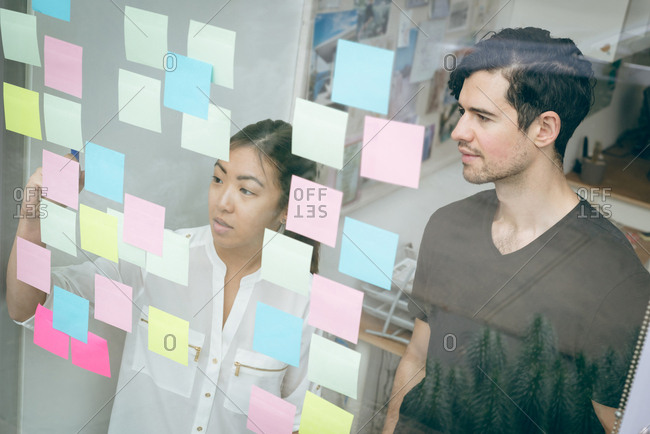 Business executives discussing over sticky notes in office
