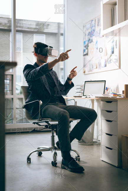 Executive using virtual reality headset in office