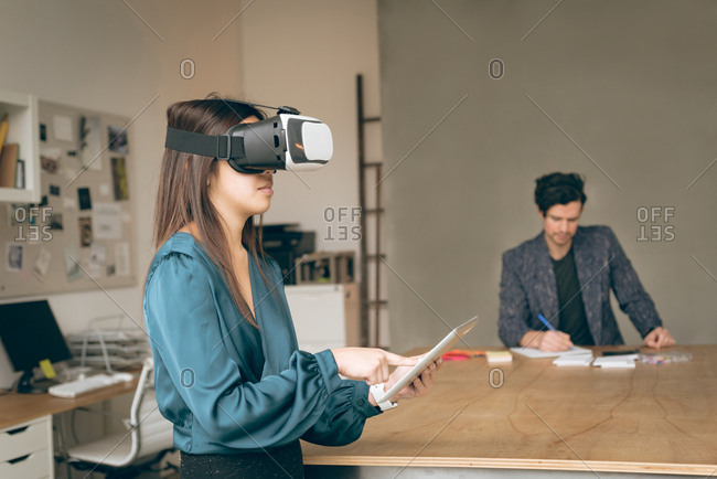 Female executive using virtual reality headset and digital tablet in office