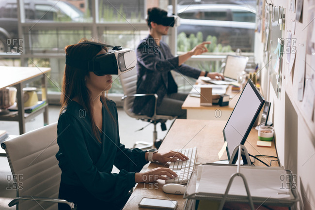 Executives working on laptop while using virtual reality headset in office