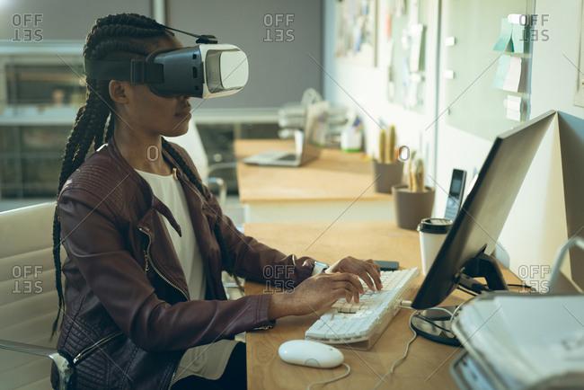 Executive working on computer while using virtual reality headset in office