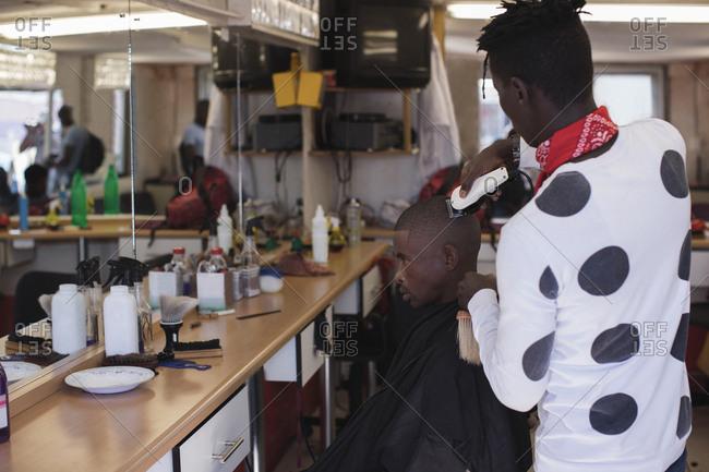 Barber shaving mans head in hair salon