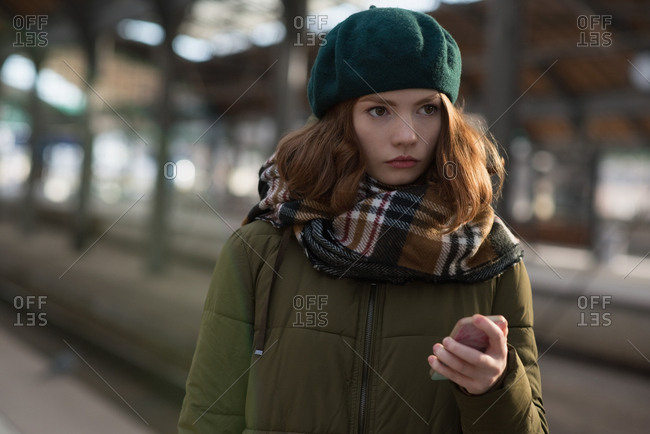 Thoughtful woman in winter clothing holding mobile phone in platform