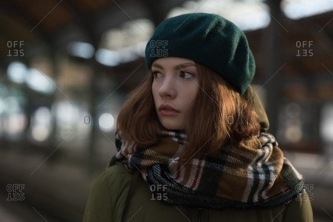 Close-up of woman in winter clothing standing at railway station