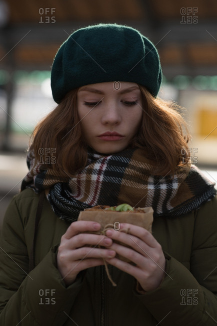 Close-up of woman in winter clothing having a wrap at railway station