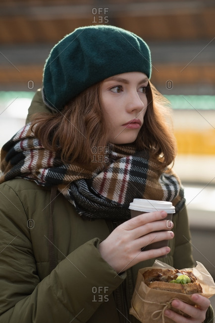 Woman in winter clothing having a wrap and coffee in railway station