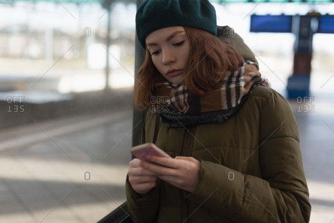 Woman in winter clothing using mobile phone in railway station