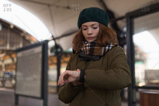 Beautiful woman in winter clothing looking at smartwatch