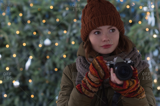 Beautiful woman in winter clothing holding vintage camera