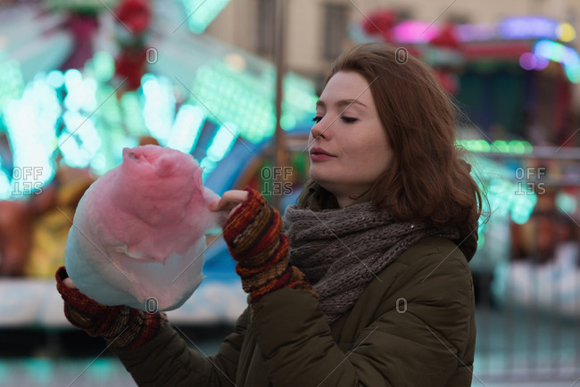 Woman in winter clothing having candy floss in amusement park