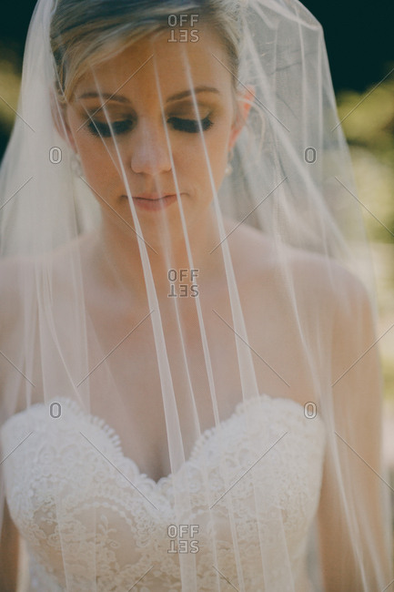 Close up  of veiled bride walking down aisle