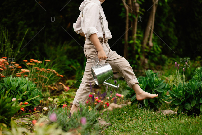 Little boy walking barefoot with a watering can