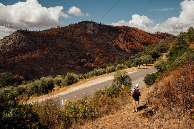 A man with a backpack walking in the hills of Vila Velha de Rodao, Portugal