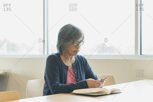 Filipino woman texting on cell phone in library