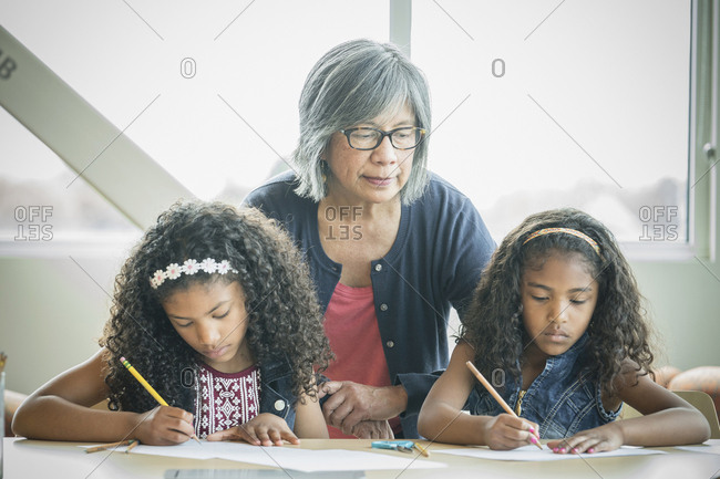 Teacher watching students writing on test