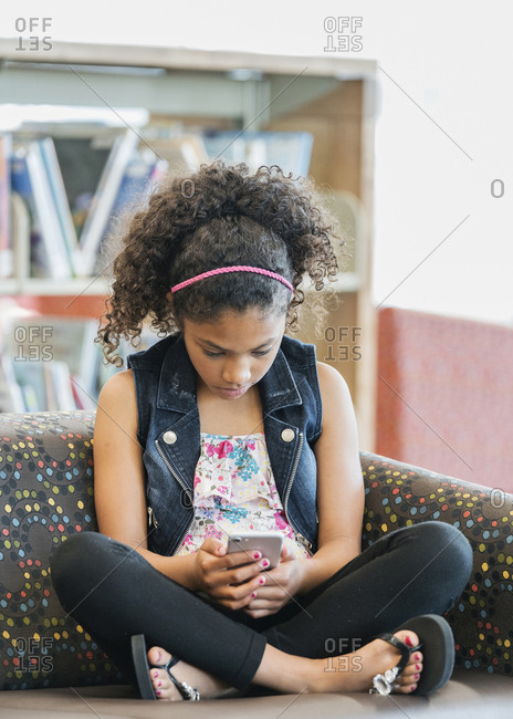 Serious mixed race girl on sofa in library texting on cell phone