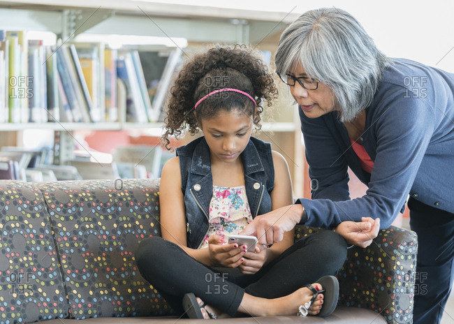 Teacher helping girl on sofa in library with cell phone