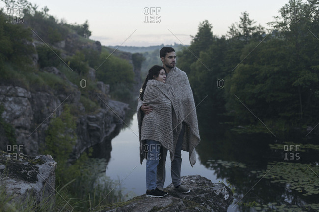 Caucasian couple wrapped in blanket standing on rock near river