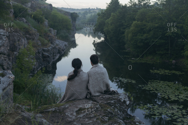 Caucasian couple wrapped in blanket sitting on rock admiring river