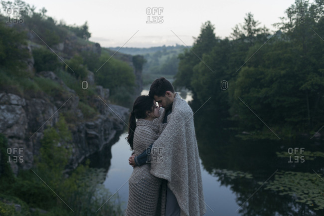 Caucasian couple wrapped in blanket hugging near river