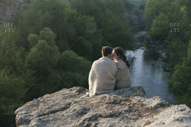 Caucasian couple wrapped in blanket kissing on rock near river