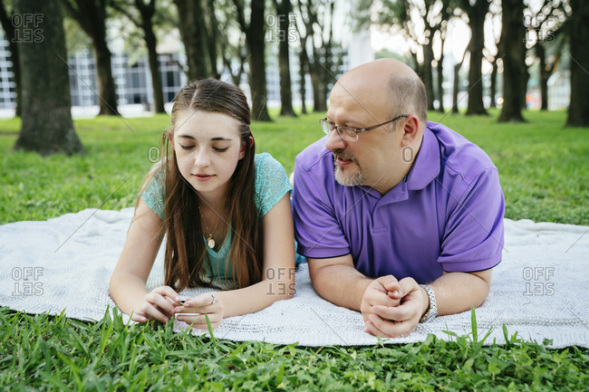 Serious Caucasian father and daughter talking on blanket in park