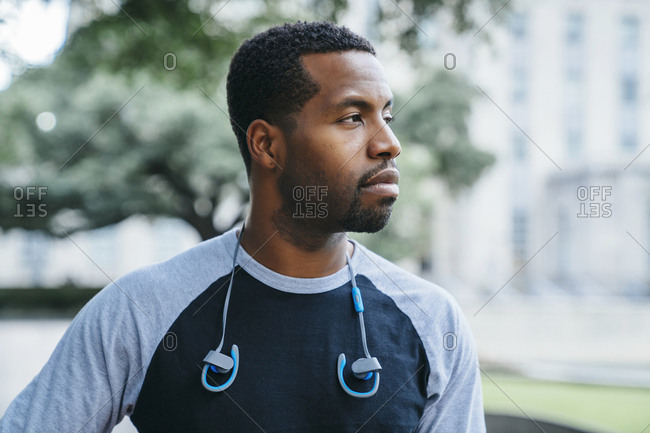 Serious Black man with ear buds looking away
