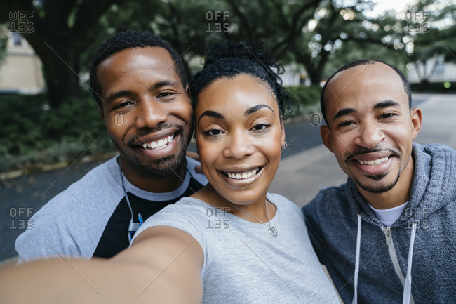 Smiling Black friends posing for cell phone selfie