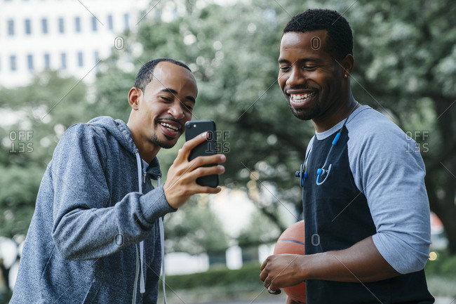 Smiling Black men texting on cell phone