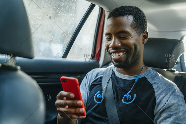 Smiling Black man texting on cell phone in car