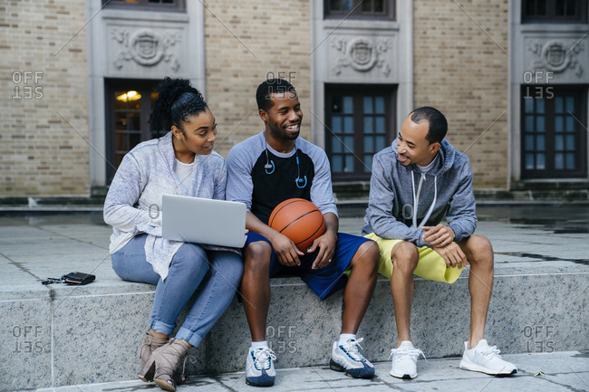 Black friends sitting on concrete with basketball and laptop
