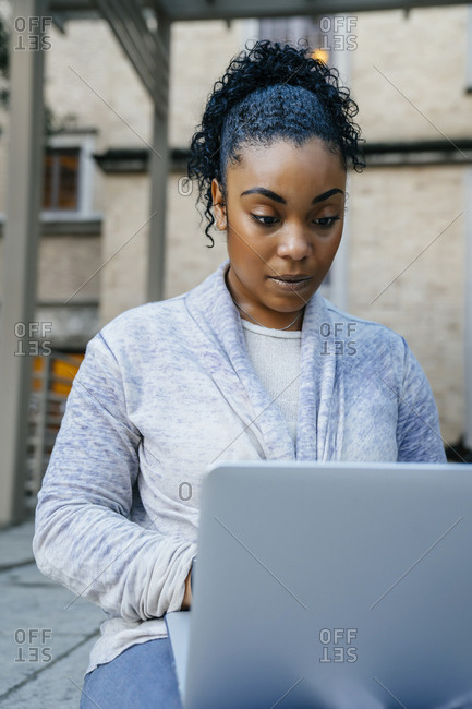 Serious Black woman using laptop outdoors