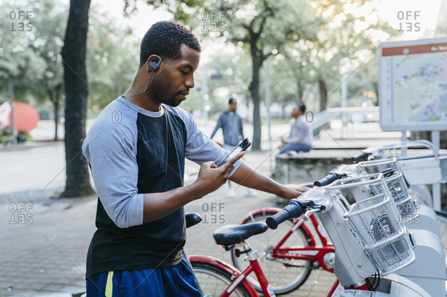 Black man paying for bicycle rental with cell phone