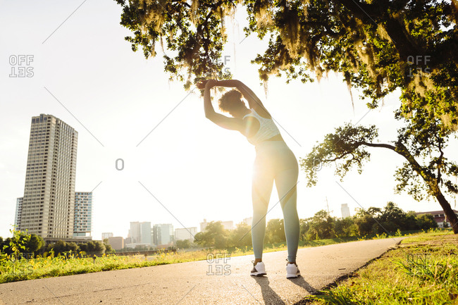 Mixed Race woman stretching on running path in park
