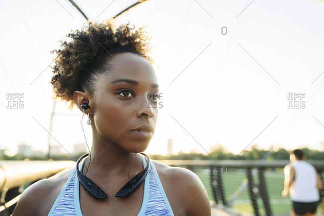 Mixed Race woman listening to ear buds on bridge