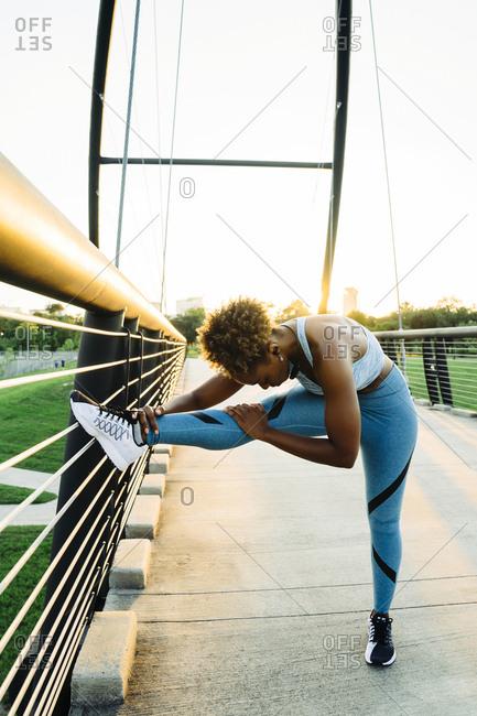Mixed race woman stretching leg on bridge railing