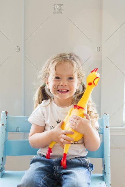 Smiling Caucasian girl holding rubber chicken