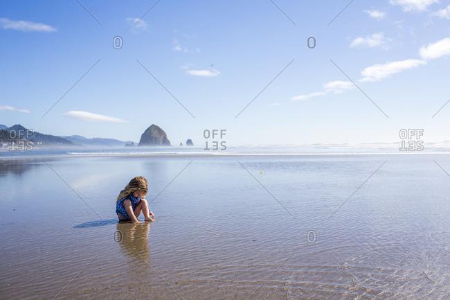 Caucasian girl sitting on beach in ocean waves