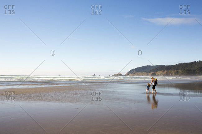 Caucasian family holding hands and walking on beach
