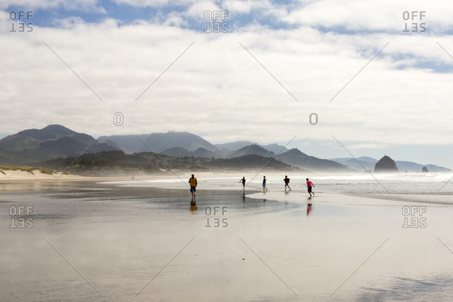 Distant people running on beach